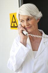 Senior woman working at laboratory making a call - RMAF000199