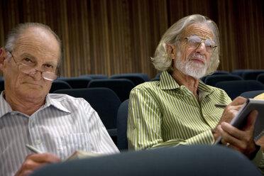 Two senior men sitting in auditorium taking notes - RMAF000205