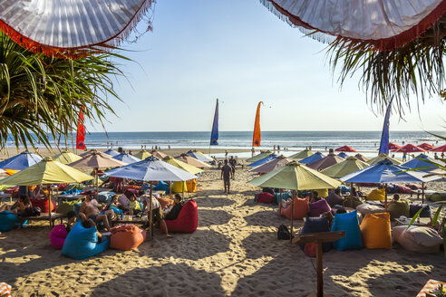 Indonesia, Bali, Denpasar, Tourists under colorful sunshades at Kuta beach - WE000401