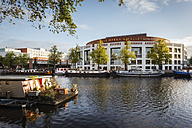 Netherlands, Amsterdam, Houseboat at Amstel river with Het Muziektheater in background - EVGF002492