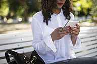Young woman sitting on park bench using her smartphone, close-up - RAEF000616