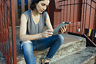 USA, New York City, woman sitting on stairs using digital tablet - GIOF000380