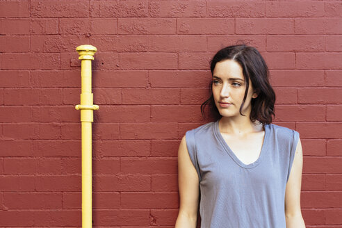 Portrait of woman leaning against red brick wall - GIOF000389