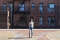 USA, New York City, Manhattan, young woman standing on a playground - GIOF000398