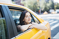 USA, New York City, portrait of young woman leaning out of window of a yellow cab - GIOF000407