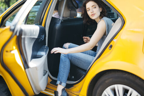 USA, New York City, portrait of  young woman getting on a yellow cab - GIOF000410