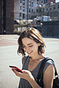 USA, New York City, Manhattan, smiling young woman looking at her smartphone - GIOF000419