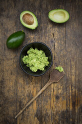 Bowl of Guacamole, cooking spoon and whole and sliced avocados on dark wood - LVF004105