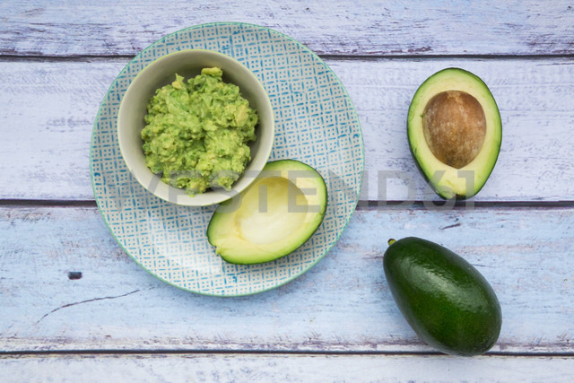 Bowl of Guacamole and whole and sliced avocados on light blue wood - LVF004108