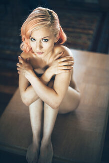 Sexy blond woman sitting naked on table, covering breasts - EHF000308