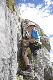Austria, Tyrol, Rofan mountains, boy climbing - JEDF000261