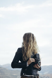 Woman with obscured face holding vintage camera - JPF000067