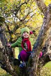 Portrait of smiling little girl sitting on tree trunk - LVF004117
