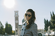 Italy, Vicenza, smiling brunette woman wearing checkered coat and sunglasses - GIOF000458