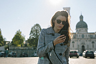 Italy, Vicenza, woman wearing checkered coat and sunglasses looking at cell phone - GIOF000461