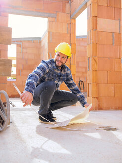 Portrait of foreman with construction plan and pocket rule at construction site - LAF001540