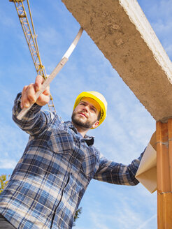 Portrait of foreman with construction plan and pocket rule checking construktion work - LAF001543