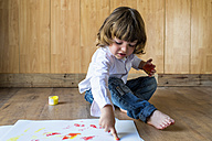 Little boy sitting on wooden floor painting with finger colours - KIJF000001