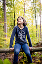 Portrait of happy girl sitting on a pole in the forest - LVF004145