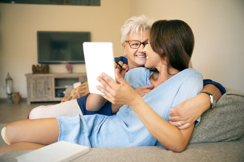 Happy senior woman and adult daughter on couch with digital tablet - TOYF001423