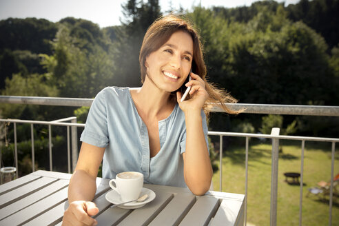 Woman on balcony with cup of coffee on the phone - TOYF001429
