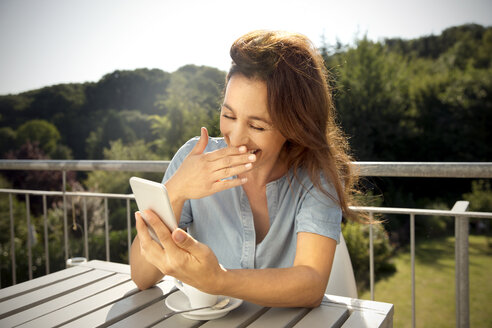 Laughing woman on balcony with cup of coffee looking on cell phone - TOYF001432