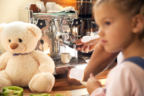 Girl with teddy bear in kitchen with father using coffee machine - TOYF001438