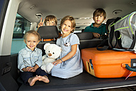Happy kids in car boot with teddy - TOYF001444