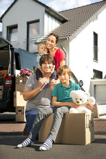 Happy family with two sons moving house - TOYF001456