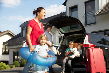 Happy family with floating tyre in driveway - TOYF001459