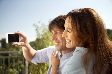 Happy couple outdoors taking a selfie - TOYF001462