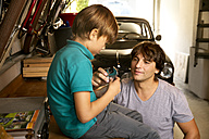 Father and son in garage with vintage car and tools - TOYF001465