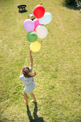 Woman standing in garden holding colorful balloons - TOYF001468