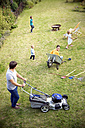 Father mowing the lawn in garden with family playing in grass - TOYF001471
