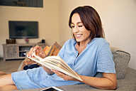 Smiling woman reading a book on couch - TOYF001474