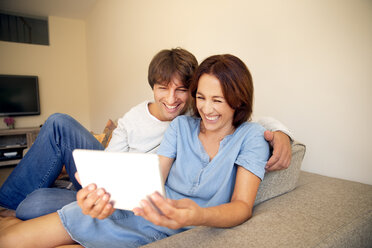 Happy couple relaxing on couch looking at digital tablet - TOYF001480