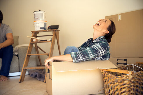 Laughing woman in cardboard box with man in background - TOYF001486