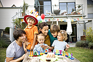 Happy family having a children's birthday party in garden - TOYF001489