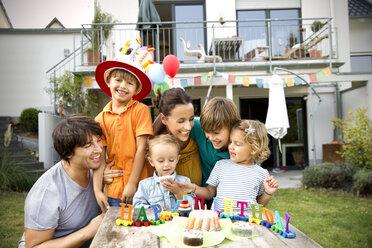 Happy family having a children's birthday party in garden - TOYF001489