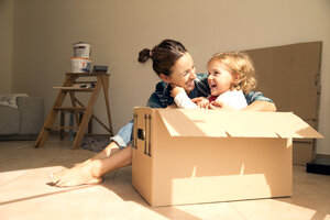 Laughing woman with daughter sitting in cardboard box - TOYF001492