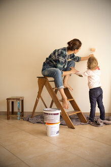Mother and daughter painting a wall - TOYF001495
