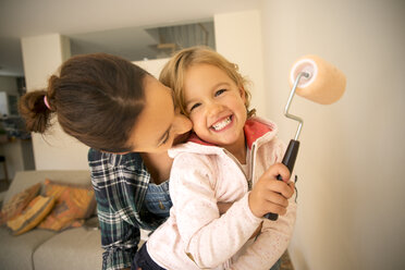 Happy woman with daughter painting a wall - TOYF001498