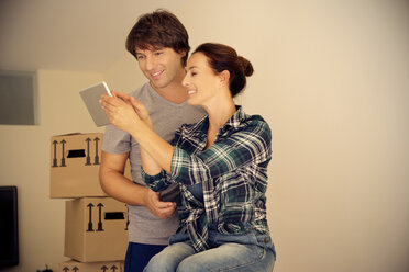 Smiling couple looking at digital tablet with cardboard boxes in background - TOYF001504