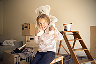 Girl with teddy bear and cardboard boxes in background - TOYF001510