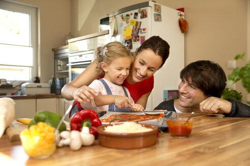 Happy family in kitchen preparing pizza - TOYF001513