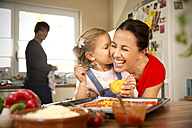 Happy mother and daughter in kitchen preparing pizza with father in background - TOYF001516