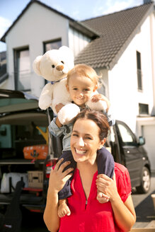 Mother carrying son with teddy bear on shoulders, standing in front of home - TOYF001522