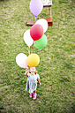 Girl standing in garden holding colorful balloons - TOYF001525