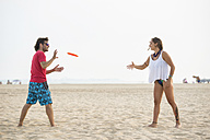 Spain, Cadiz, El Puerto de Santa Maria, Couple playing frisbee on the beach - KIJF000011