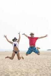 Spain, Cadiz, El Puerto de Santa Maria, Couple jumping on the beach - KIJF000017